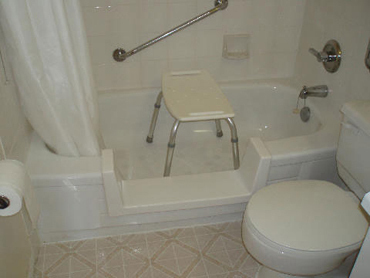 Tub cutout with shower seat and grab bar installed by Bathway